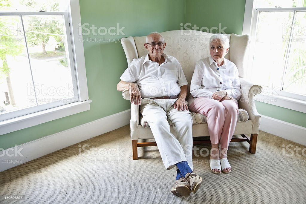 Elderly couple sitting together on love seat stock photo