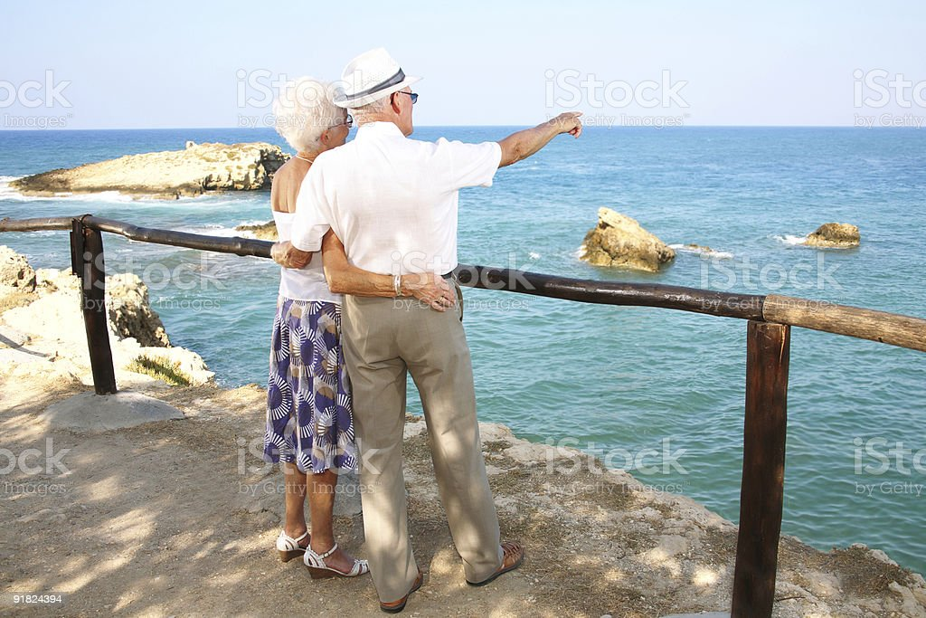 Elderly couple standing by a railing pointing to the ocean royalty-free stock photo