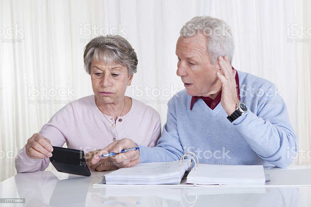 Elderly couple stressed out paying bills on limited budget royalty-free stock photo