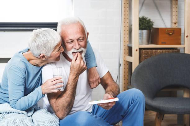Elderly couple taking medication stock photo