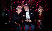 Elderly couple talking while sitting in theater. Happy man and woman are watching opera with crowd. They are spending quality time together.