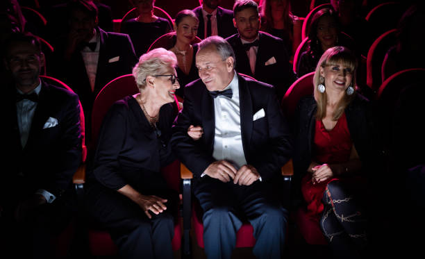 Elderly couple talking while sitting in theater Elderly couple talking while sitting in theater. Happy man and woman are watching opera with crowd. They are spending quality time together. evening wear stock pictures, royalty-free photos & images