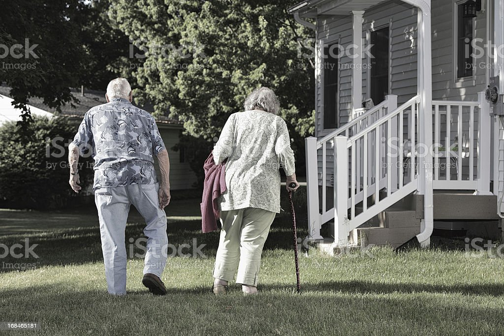 Elderly Couple Walking Slowly Together in Back Yard royalty-free stock photo