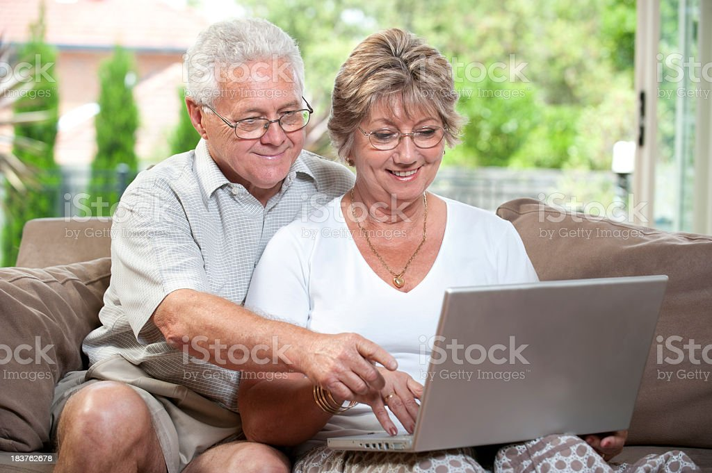 Elderly couple working on a laptop royalty-free stock photo
