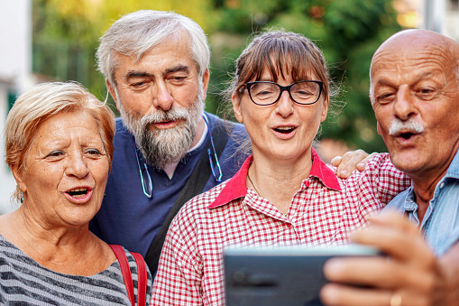 Elderly couples taking selfie with smartphone - Old friends reunion having fun outdoors with each other