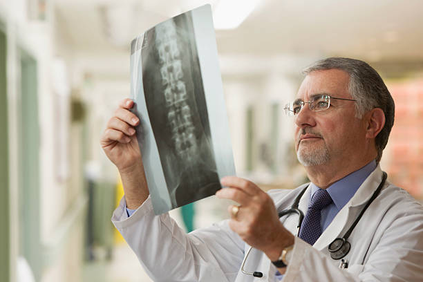 Elderly doctor looking at x-rays stock photo
