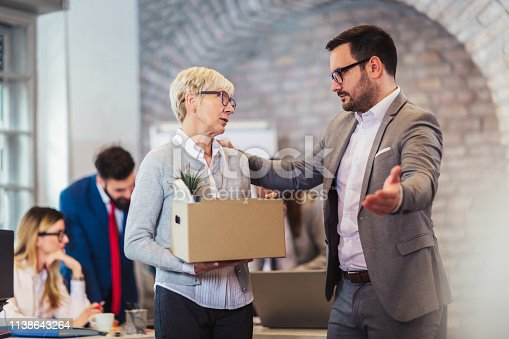 1048789678istockphoto Elderly employee leaving office with box full of belongings. Time to retire 1138643264