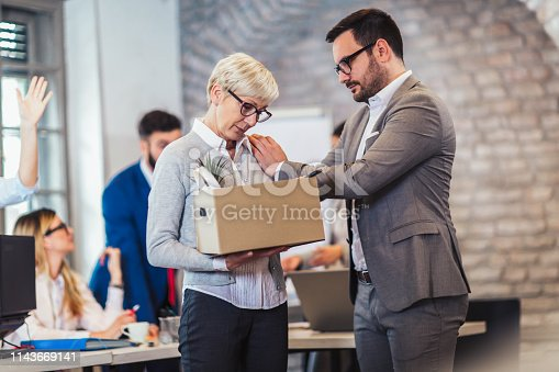 1048789678istockphoto Elderly employee leaving office with box full of belongings. Time to retire 1143669141