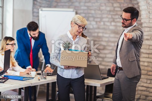 1048789678istockphoto Elderly employee leaving office with box full of belongings. Time to retire 1156322136