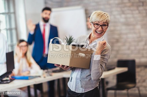 1048789678istockphoto Elderly employee leaving office with box full of belongings. Time to retire 1156322722