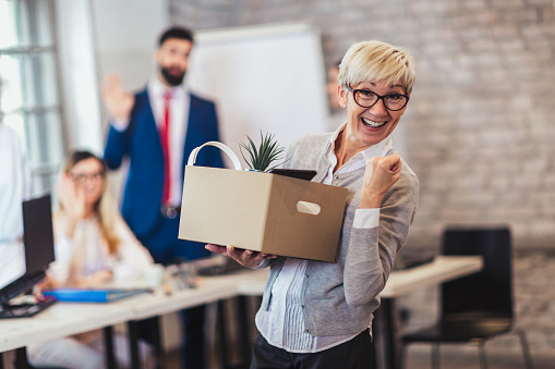 1048789678 istock photo Elderly employee leaving office with box full of belongings. Time to retire 1156322722
