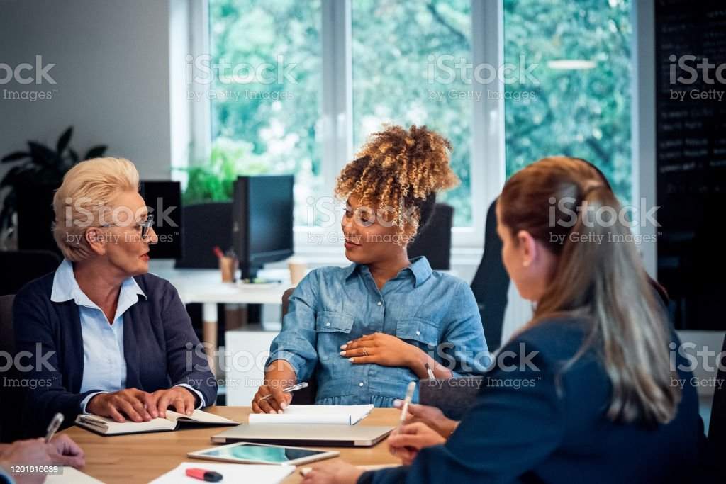 Elderly executive talking to pregnant colleague Elderly female executive talking to pregnant colleague. Businesswomen are brainstorming at desk. Business professionals are working in new office. 35-39 Years Stock Photo