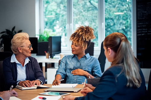 Elderly Executive Talking To Pregnant Colleague Stock Photo - Download Image Now