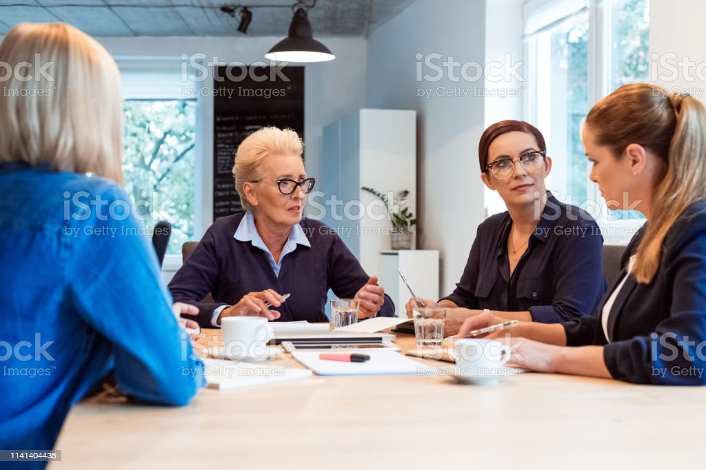 Elderly expertise discussing plan with colleagues Elderly professional discussing plan with female colleagues. Expertise are working together in new business. They are sitting in office. 35-39 Years Stock Photo