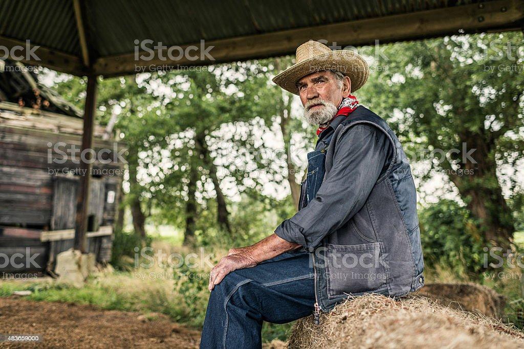 Elderly farmer sitting waiting royalty-free stock photo