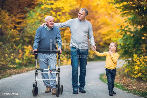 istock Elderly father adult son and grandson out for a walk in the park. 929537264