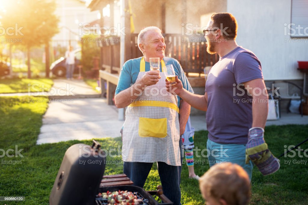 Elderly Father and mature son are saluting with the beer in front of the grill in their house backyard on a beautiful day. stock photo