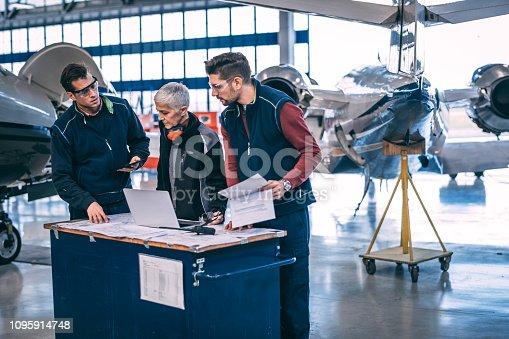 Aircraft engineer crew coordinating together in an aircraft hangar.