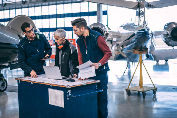 Ältere weibliche Flugzeugingenieur zu koordinieren und ihre Crew der Mechanik in einem Flugzeughangar – Foto
