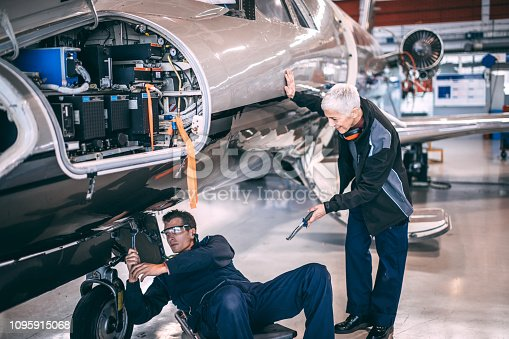 Elderly female aircraft mechanic helping her colleague who's working on the airplane's landing gear retraction system. She is passing him a tool.