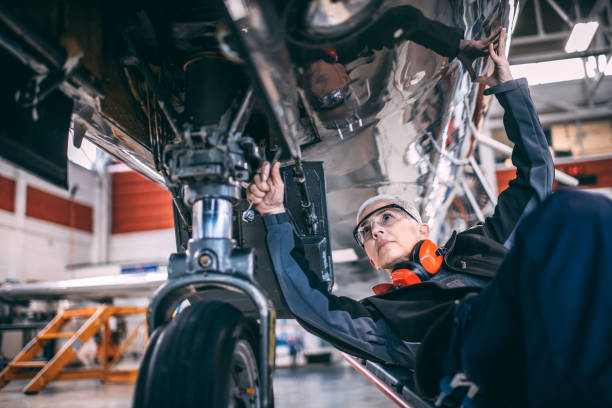 Elderly female engineer using a socket wrench while repairing or doing maintenance to the landing gear of a small airplane in a maintenance hangar Senior female mechanic using a socket wrench while repairing or doing maintenance to the landing gear of a small airplane in an aircraft maintenance hangar. socket wrench stock pictures, royalty-free photos & images