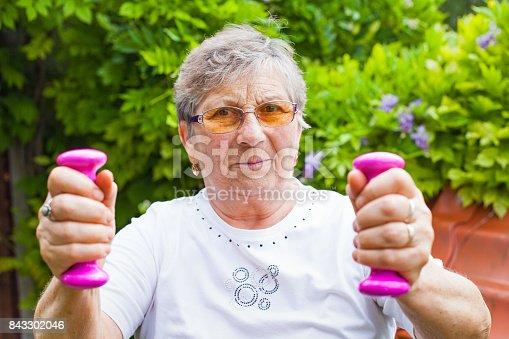 950649706istockphoto Elderly female exercising with dumbbells 843302046