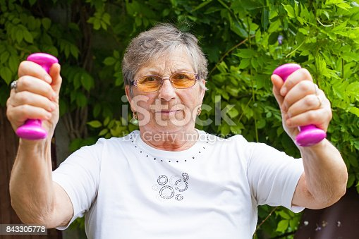 950649706istockphoto Elderly female exercising with dumbbells 843305778