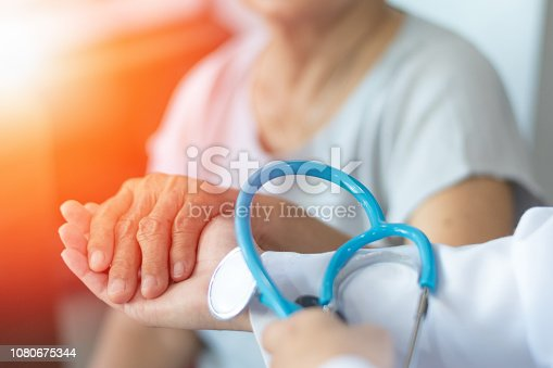 istock Elderly female hand holding hand of young caregiver at nursing home.Geriatric doctor or geriatrician concept. Doctor physician hand on happy elderly senior patient to comfort in hospital examination 1080675344