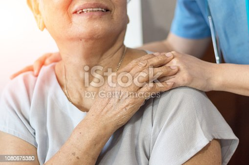 istock Elderly female hand holding hand of young caregiver at nursing home.Geriatric doctor or geriatrician concept. Doctor physician hand on happy elderly senior patient to comfort in hospital examination 1080675380