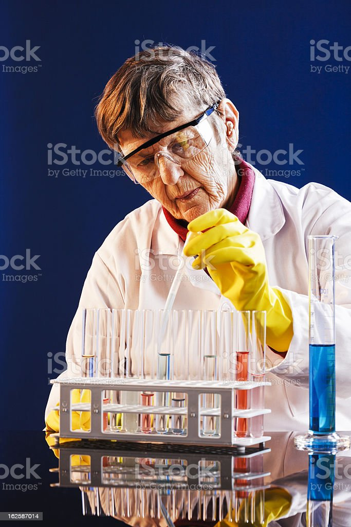 Elderly female lab worker drips liquid into test tube stock photo