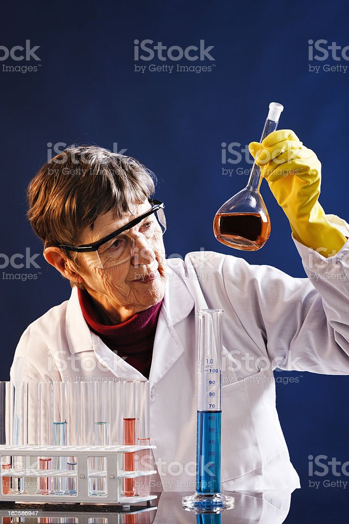 Elderly female scientist examining liquid in flask at lab bench stock photo