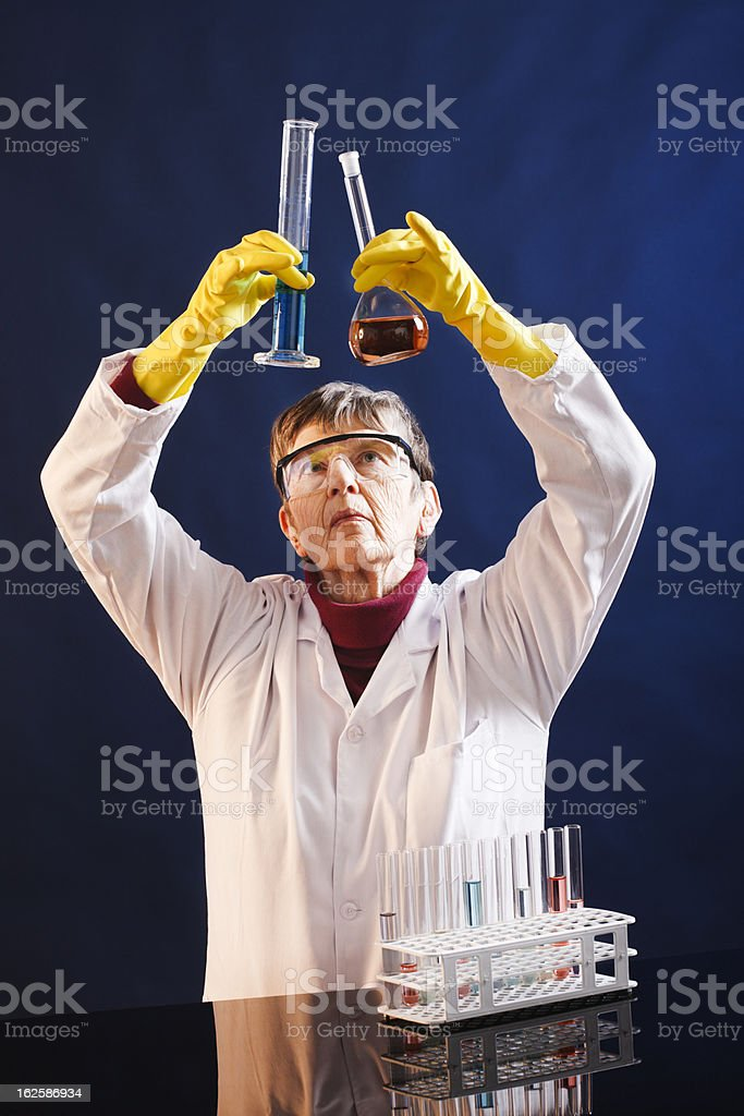 Elderly female scientist holds up two laboratory beakers, comparing contents stock photo