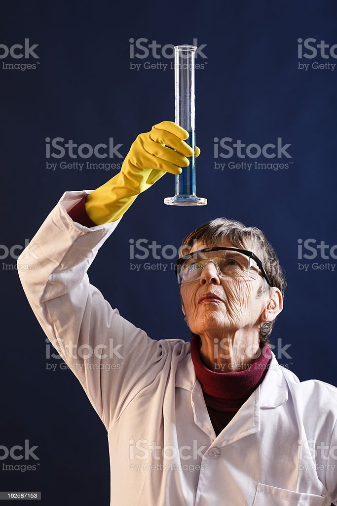 Elderly female scientist looks up, studying contents of glass beaker stock photo