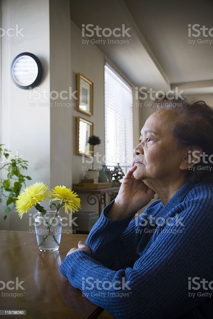 Elderly female sitting in solitude in a room stock photo