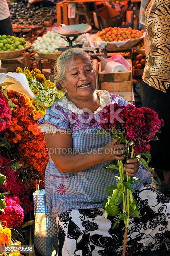 Teotitlán, Oaxaca, Mexico- October 31, 2009: An elderly woman selling flowers in a market in Teotitlán