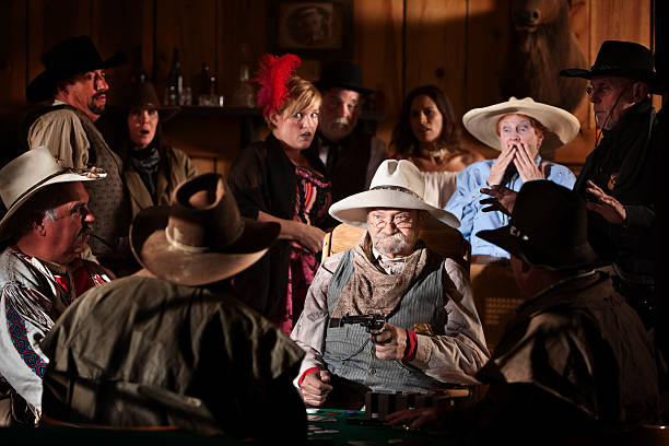 Elderly Gambler Points Gun Elderly man holds up players in a poker game saloon stock pictures, royalty-free photos & images
