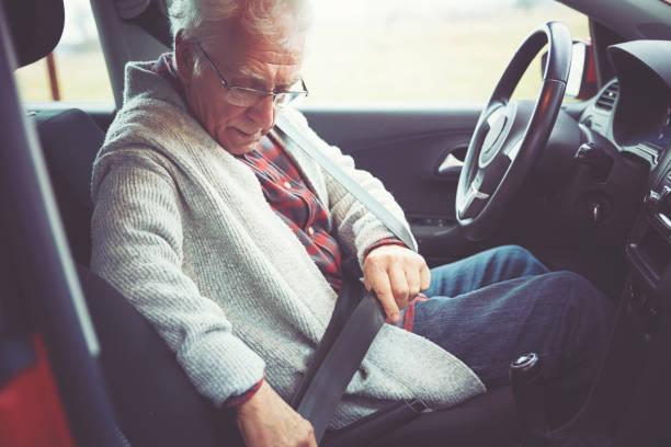 Elderly gentleman fastening a seat belt before he drives his car stock photo