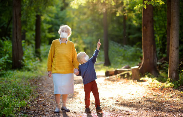 Elderly grandmother and little grandchild wearing facemask walking together in sunny summer park. Grandma and grandson. Lifting virus lockdown orders. Social distancing. stock photo