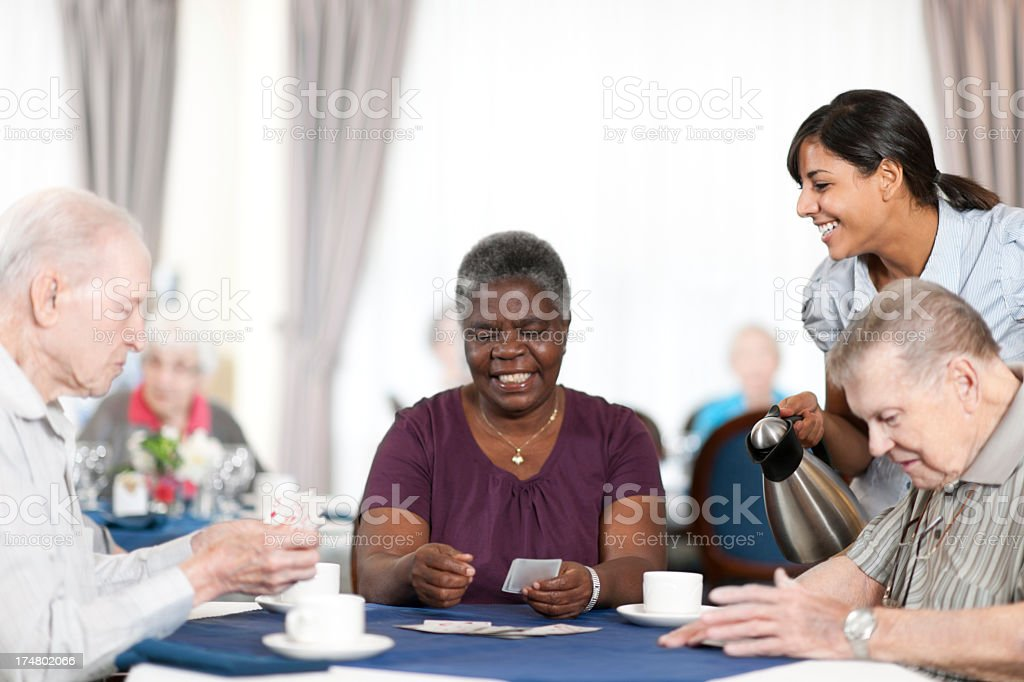 Elderly group happily playing cards. stock photo