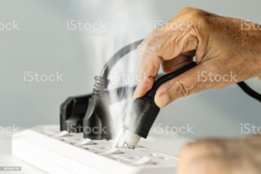 Elderly hand with electrical outlet spark stock photo