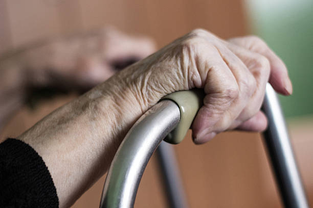 Elderly hands on a walker stock photo