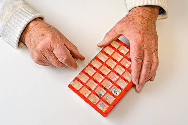 Elderly hands open a pill organiser stock photo