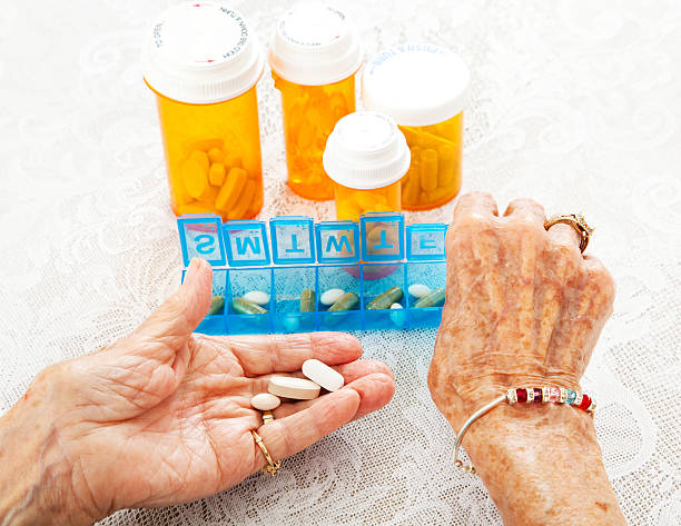 Elderly Hands Sorting Pills Closeup view of an eighty year old senior woman's hands as she sorts her prescription medicine. pill container stock pictures, royalty-free photos & images