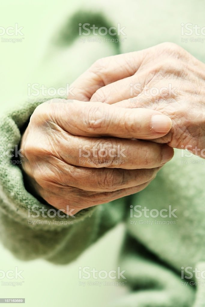 Elderly Hands with a Green Sweater stock photo