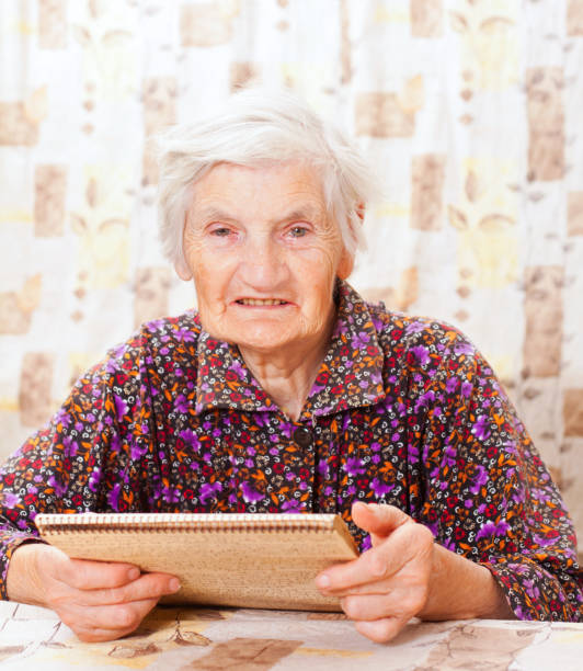 Elderly happy woman read something from the book stock photo