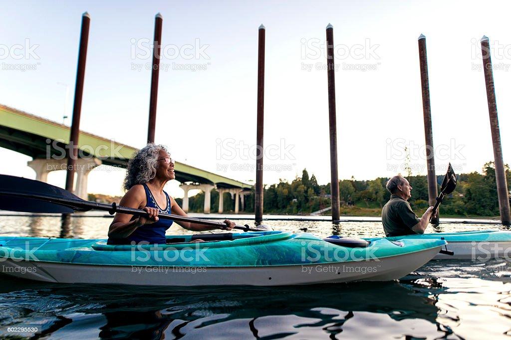 Elderly heterosexual couple kayaking on the river stock photo
