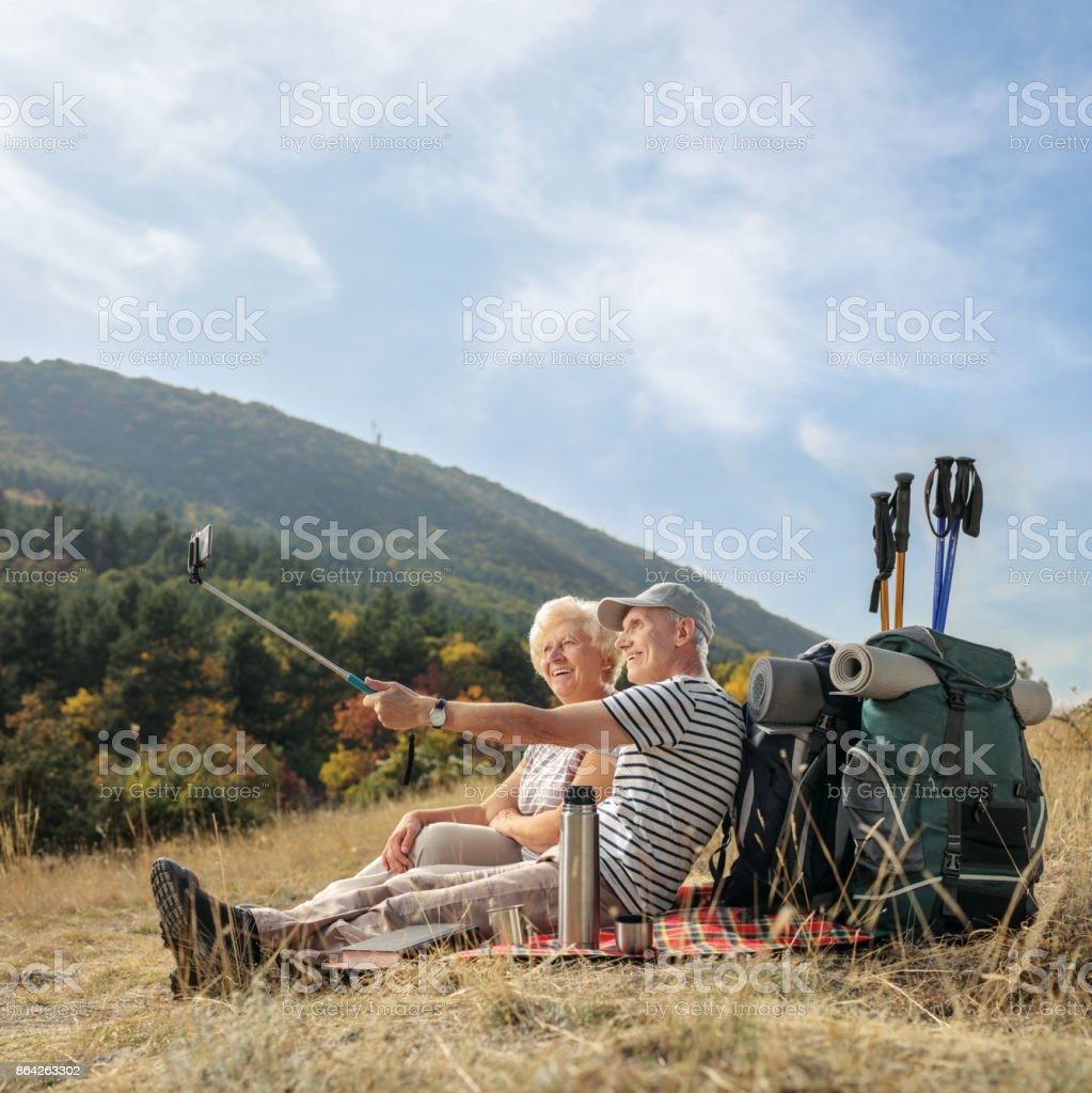 Elderly hiker taking a selfie outdoors royalty-free stock photo