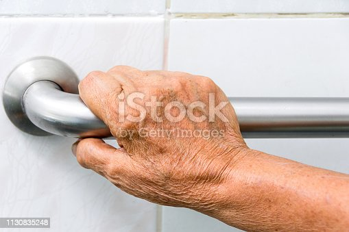 elderly holding a grab bars in a bathroom
