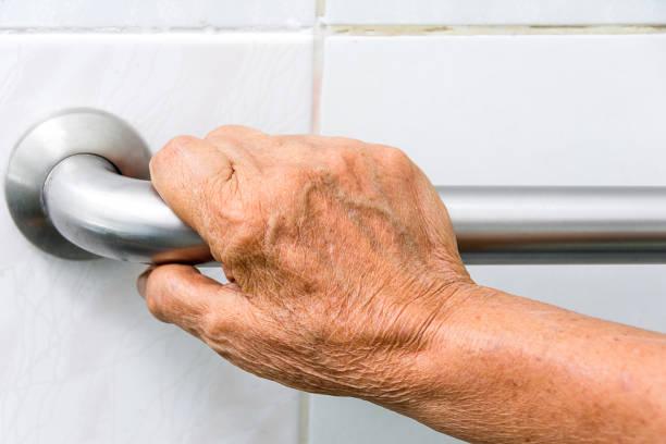ouderen met een handgrepen in een badkamer - veiligheidshek stockfoto's en -beelden