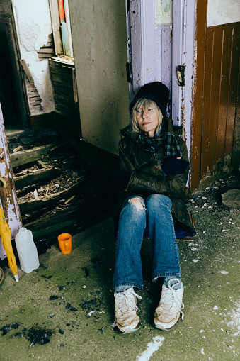 Elderly homeless senior woman sitting on the floor of an abandoned ruin